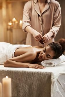 Нежная африканская женщина ослабляя наслаждающся здоровым массажем курорта с маслом.