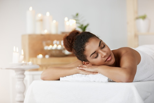 Tender african woman resting relaxing with closed eyes in spa salon.