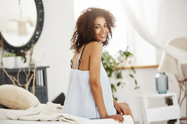 Tender african woman in sleepwear sitting on bed at home smiling.