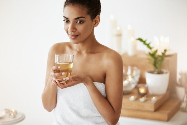 Donna africana tenera che sorride giudicando vetro con tè che si rilassa nel salone della stazione termale.