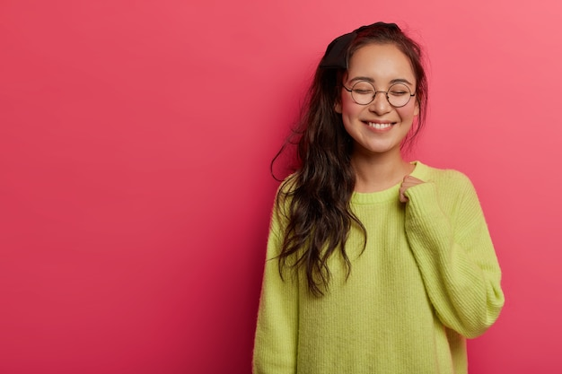 Tender alluring female model grins happily at camera, keeps arm raised, wears green jumper and round transparent glasses, thinks about something pleasant