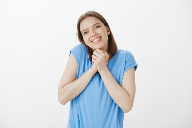 優しくて愛らしい若い女性が手を握りしめ、感謝の気持ちを込めて、贈り物を受け取る