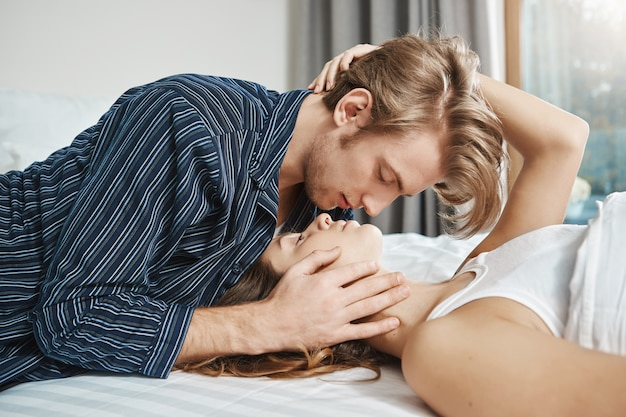 ベッドで横になっている優しく魅力的なカップル、寝室でロマンチックなショット。ボーイフレンドは、化粧せずに、髪の毛が散らかっていても彼女を愛しています。彼女は彼をより良い人にする