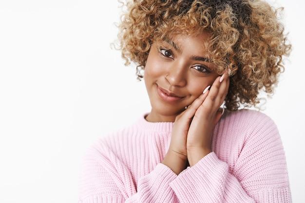 곱슬한 금발 머리를 손바닥에 기대고 있는 부드럽고 여성스러운 아프리카계 미국인 여자친구는 카메라를 보며 달콤하고 귀여운 미소를 지으며 흰 벽 너머로 사랑을 바라보며 로맨스를 느끼고 있습니다.