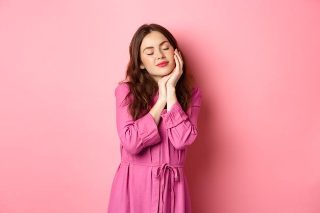 Нежная и женственная женщина нежно прикасается к ее лицу, закрывает глаза и мечтает о чем-то романтичном, чувствуя мягкую кожу лица после косметики, розовую стену.