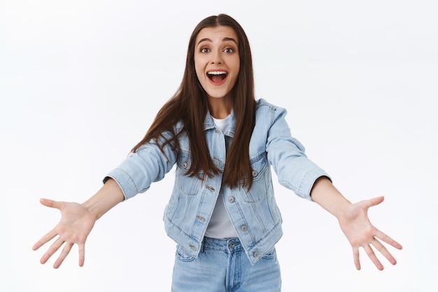 デニムジャケットを着た優しくてフレンドリーな魅力的なブルネットの女の子、ジーンズは友達に会い、手を広げて誰かを歓迎し、暖かい抱擁や抱擁を与え、うまくいけば笑顔で、ハロウィーンパーティーでおなじみの人に会います