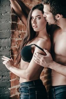 부드럽고 관능적입니다. 잘생긴 젊은 벗은 남자가 벽돌 벽 근처에 서 있는 동안 아름다운 여자 친구의 브래지어 끈을 당기고 있습니다.