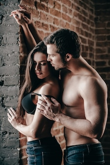 부드럽고 관능적입니다. 남자가 그의 여자 친구에게서 브래지어를 벗는 동안 서로 결합하는 청바지에 아름 다운 젊은 벗은 부부의 측면보기