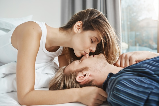 Tender and attractive woman gently kissing her boyfriend in nose while he lies on bed with closed eyes in bedroom. romantic moment of couple in relationship after spending night together.