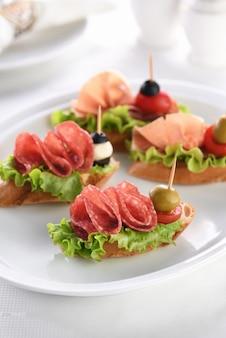 リーフレタス、サラミまたはパルマハム、トマト、モッツァレラチーズ、オリーブを添えた柔らかいバゲットカナッペ。パーティーでの珍味盛り合わせ盛り合わせ。