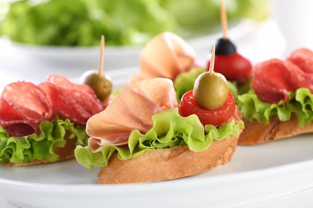 Нежные канапе из багета с салями из листового салата или пармской ветчиной, помидорами, моцареллой и оливками