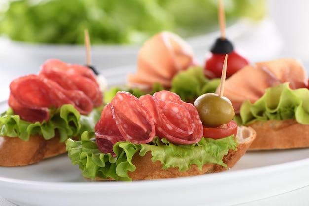 Нежные канапе из багета с салями из листового салата или пармской ветчиной с помидорами и моцареллой