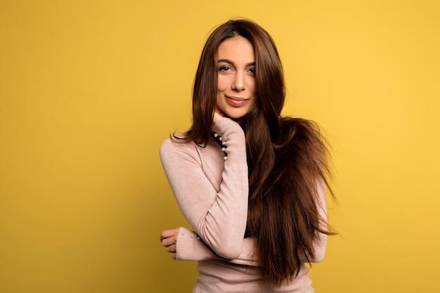 なブルネットの女性のスタジオ撮影をポーズピンクのシャツを着ている黒い髪の美しい優しい美しい少女。