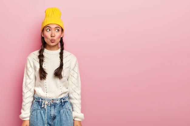 Tenera e bella donna coreana tiene le labbra arrotondate, pensa a qualcosa, immagina la scena in mente, vestita con abiti alla moda, posa contro il muro rosa
