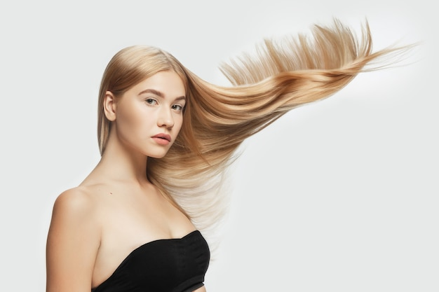 Tender. beautiful model with long smooth, flying blonde hair on white studio background. young caucasian model with well-kept skin and hair blowing on air. concept of salon care, beauty, fashion.