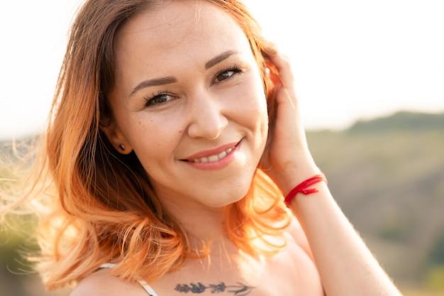 Нежная красивая рыжеволосая девушка наслаждается закатом в поле с холмом