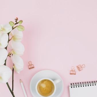 부드러운 아름다운 하얀 난초 꽃; 연필; 커피 컵; 분홍색 배경에 나선형 메모장 및 불독 종이 클립