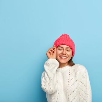 부드러운 아름다운 여인은 즐거운 것을 상상하고, 얼굴 가까이에 손을 대고, 넓게 미소를 짓고, 겨울 옷을 입고, 눈을 감고, 파란색 벽 위에 포즈를 취합니다.