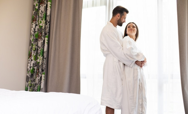 Tender and a beautiful young couple in love in white bathrobes