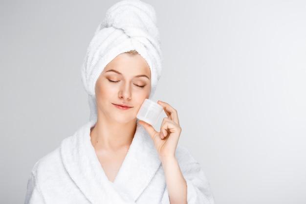 Нежная белокурая женщина с банным полотенцем на волосах показывает крем