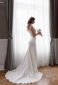 Tender blonde caucasian bride in stylish dress with white wedding bouquet is standing near the window