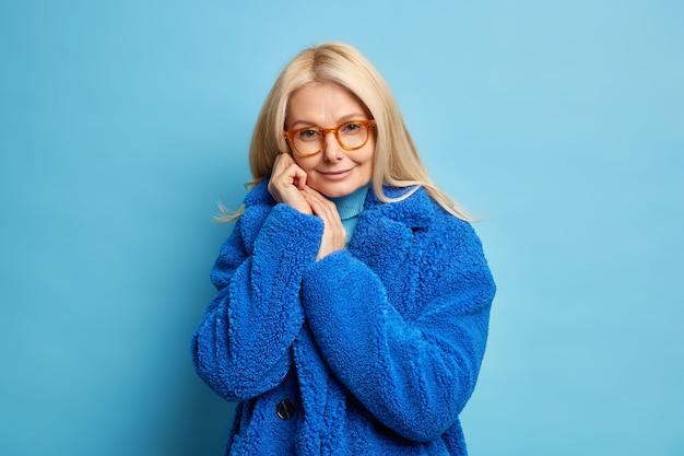 優しい金髪のヨーロッパ人女性が顔の近くで手を保ち、気持ちよく見えるのは自信に満ちた表情で、おしゃれな冬の毛皮のコートを着ています。
