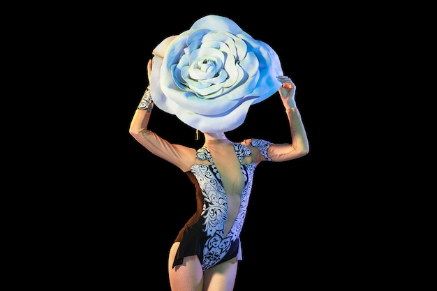 Tender and bloom. young female dancer with huge floral hat in neon light on black wall.