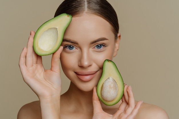 Tender blue eyed woman looks directly at camera holds halves of avocado near face