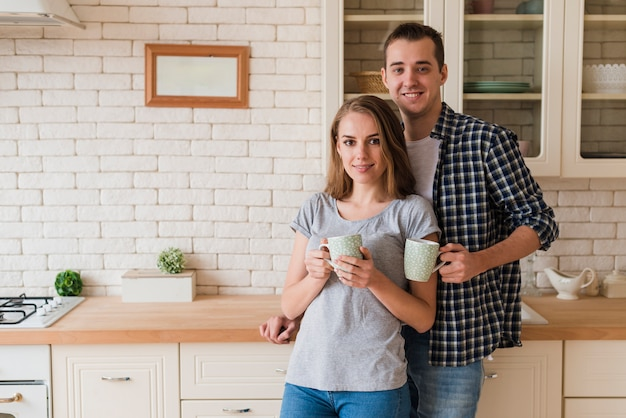 Tender bonding couple drinking brew and standing in kitchen