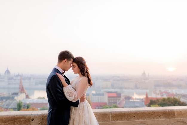 Tender bride and groom are hugging with beautiful view of a big city in the warm summer evening