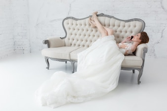 Tender bride talking over cell phone lying on classic sofa.