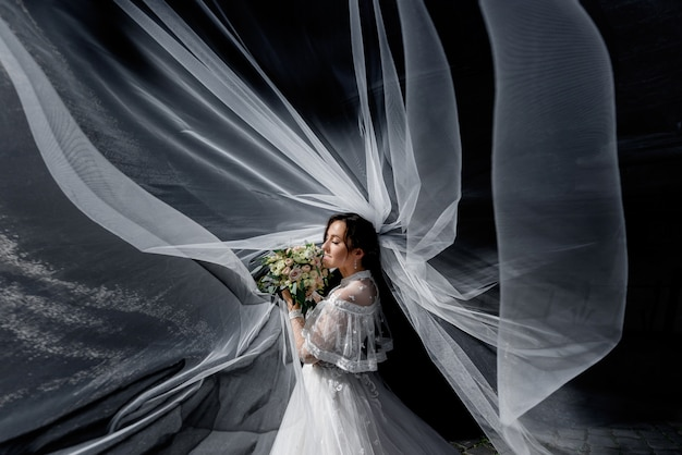 Tender bride with wedding bouquet in the sun rays with spreaded around veil