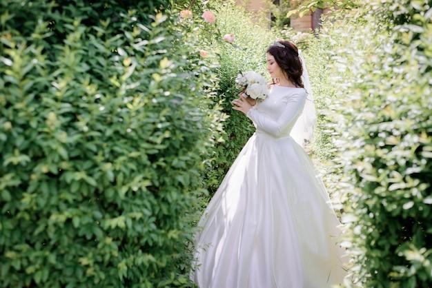 緑豊かな庭園に立っている優しいブルネットの花嫁とウェディングブーケの香りを嗅ぐ