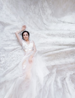 Tender brunette caucasian bride is laying on the fabric of a luxury wedding dress