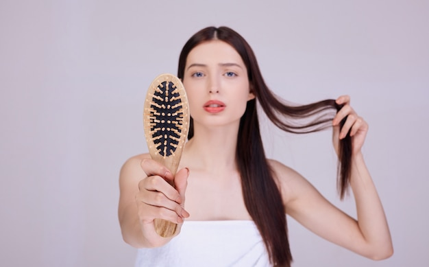 A tender brunette with a wooden comb holds on to her hair.