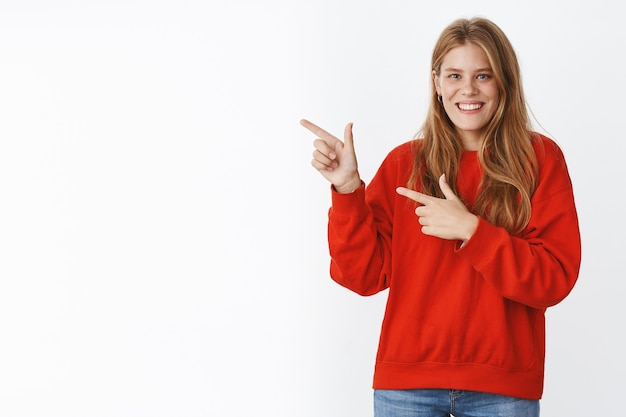 Tender charismatic attractive european woman with fair hair, freckles and blue eyes pointing at upper left corner gazing with broad entertained smile giving advice showing cool copy space