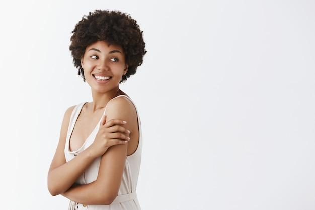 Tenera e affascinante bella donna afro-americana con l'acconciatura riccia girando a destra con un sorriso sensuale e felice, toccando delicatamente il braccio in piedi