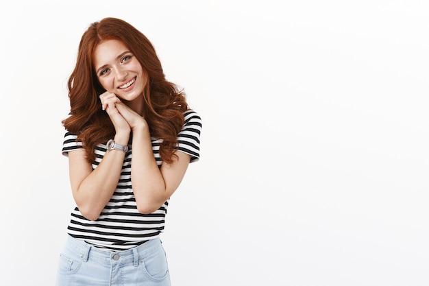 Tenera e affascinante ragazza dai capelli rossi che sospira romanticamente, appoggia la testa sulla spalla e sorride commossa, sentendosi felice, guardando un cucciolo carino che gioca, in piedi felice muro bianco