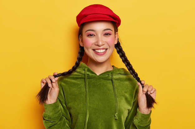 Tender charming young woman with korean appearance, beams from happiness and joy, holds two braids