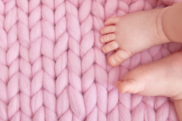 Tender child's legs on a knitted blanket