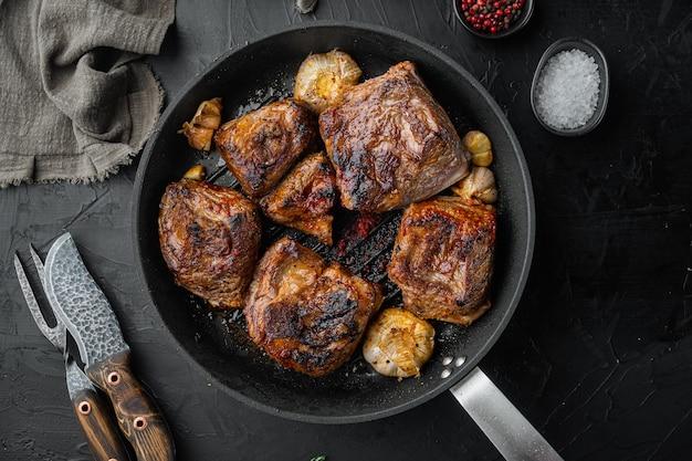 검은 돌 배경에 맛있고 풍부한 소스 세트의 부드러운 요리 갈비, 평면도 평면 누워