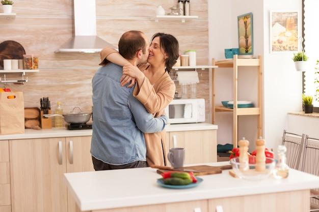 부엌에서 춤추는 부드러운 커플과 식탁에 신선한 야채. 아내와 남편의 사랑, 로맨스, 부드러운 순간, 집에서의 재미와 행복, 공생 음악 쾌활하고 미소