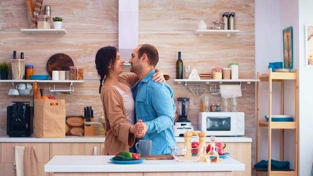 Tender couple dancing in kitchen and fresh vegetables on table. cheerful happy young family together dance. fun love affection romance leisure romantic music for enjoynment