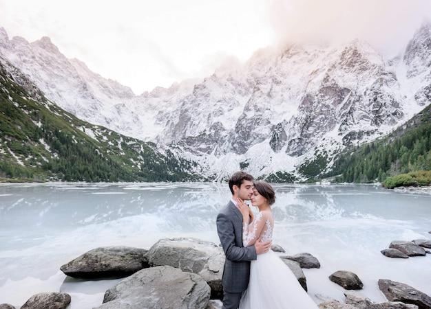 Нежная влюбленная пара в свадебных нарядах обнимается перед замерзшим озером и высокими горами, покрытыми снегом