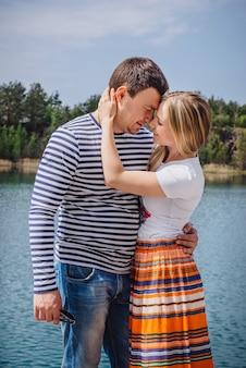 湖や川の近くでキスする優しいカップル