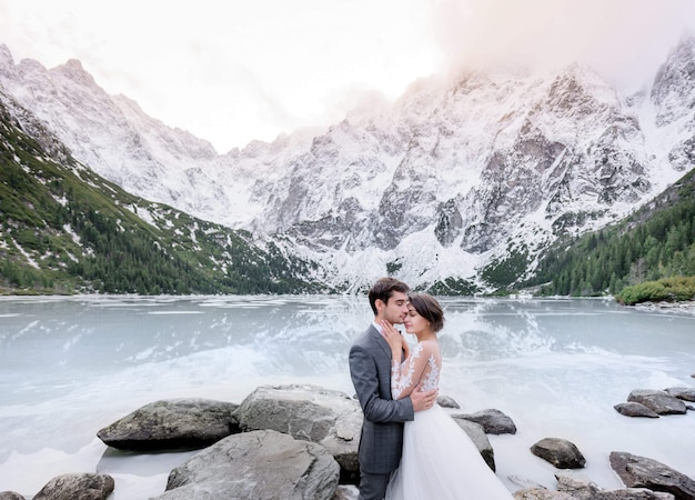 Tender couple in love dressed in wedding outfits is hugging in front of frozen lake and  high mountains covered with snow