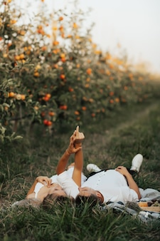 Tender couple lying on the green grass and holding hands up. young couple are having picnic in the apples orchard.