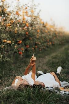 緑の草の上に横たわって、手を上げて優しいカップル。若いカップルはリンゴ園でピクニックをしています。