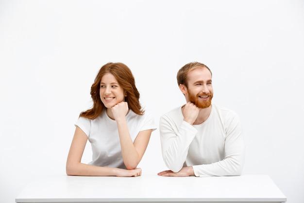 赤毛の優しいカップルがテーブルを横向きに見る