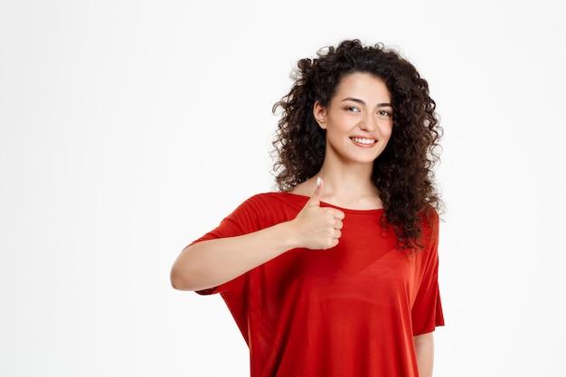 Нежная кудрявая девушка улыбается и указывая хорошо знаком на белой стене